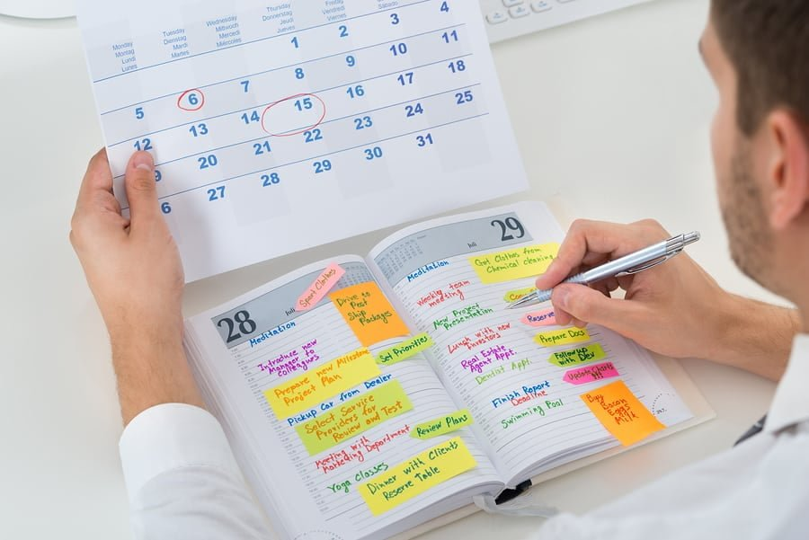 Man reviewing his schedule on calendar and day planner