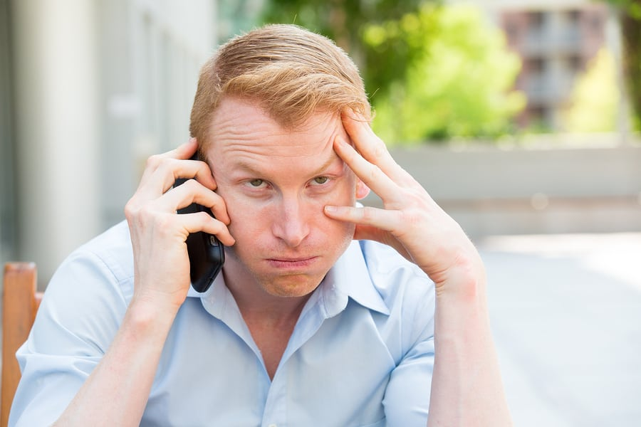 Unhappy young man on a cell phone