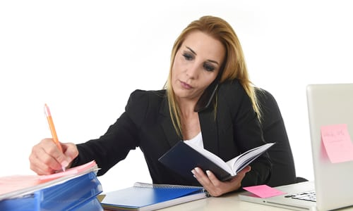 Woman on phone while trying to work at the same time