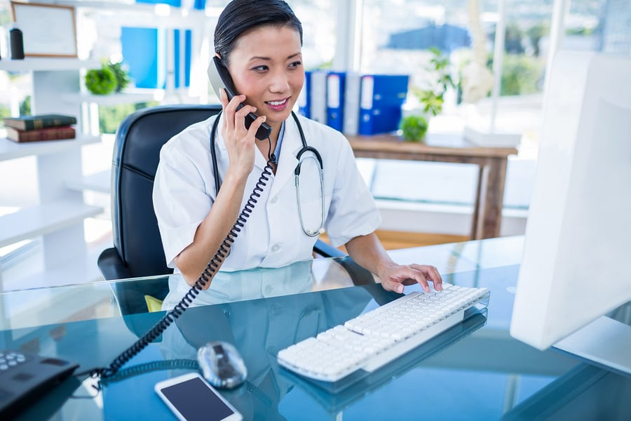 Medical professional answering phone and working on computer