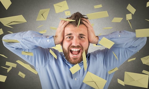 Overwhelmed man standing in mail falling from sky