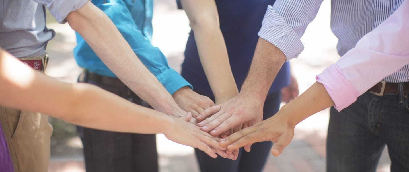 Team of people touching hands