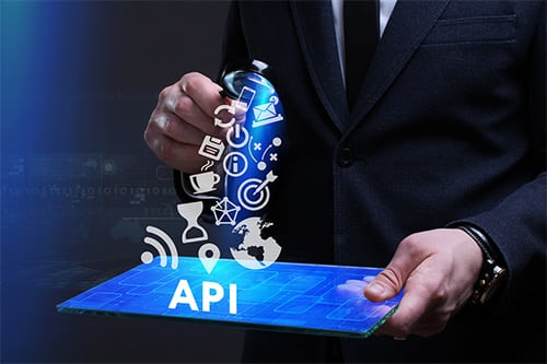 Man in business suit holding tablet with API image coming out of it