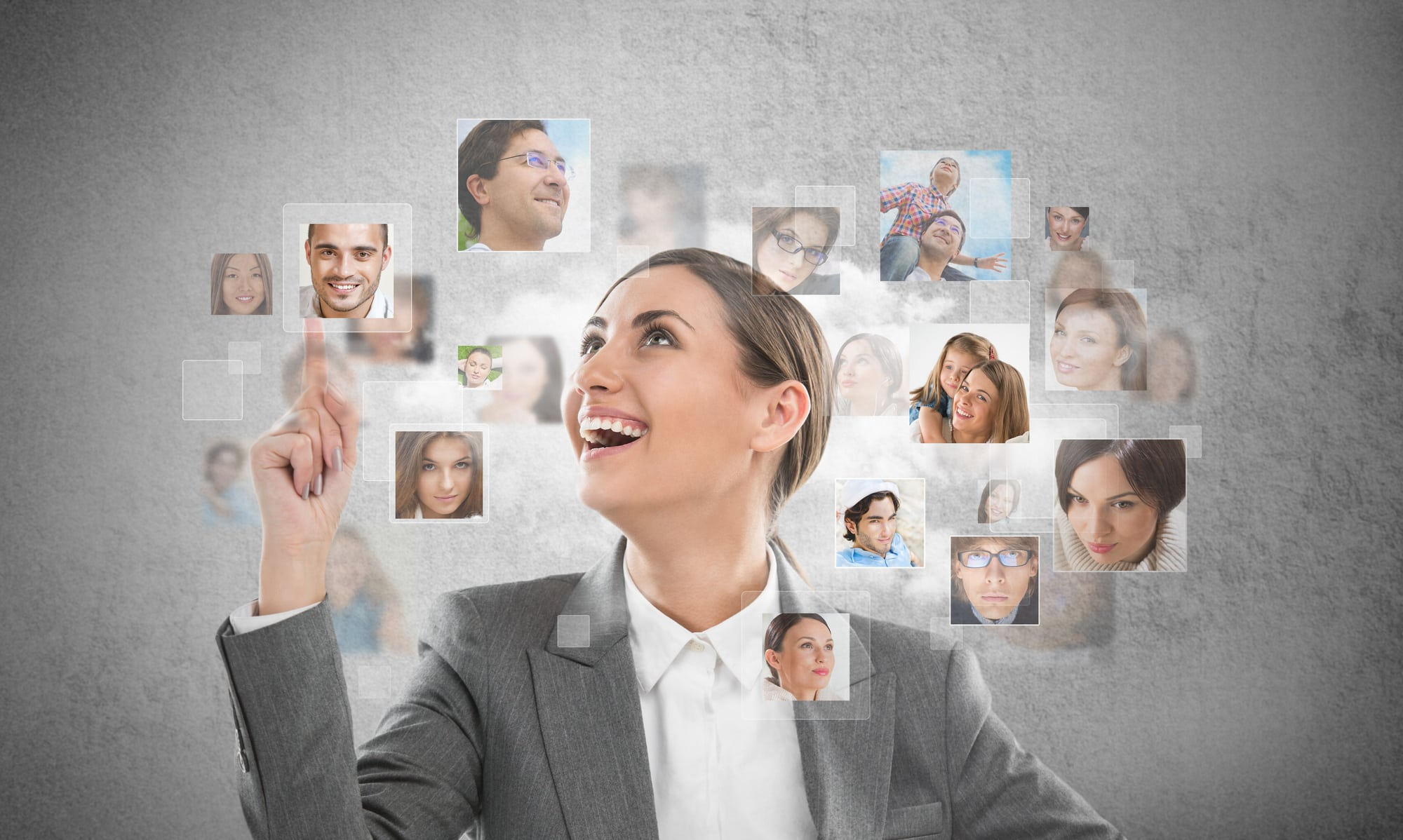 Young successful business woman looking at people portraits. International communication and recruitment concept
