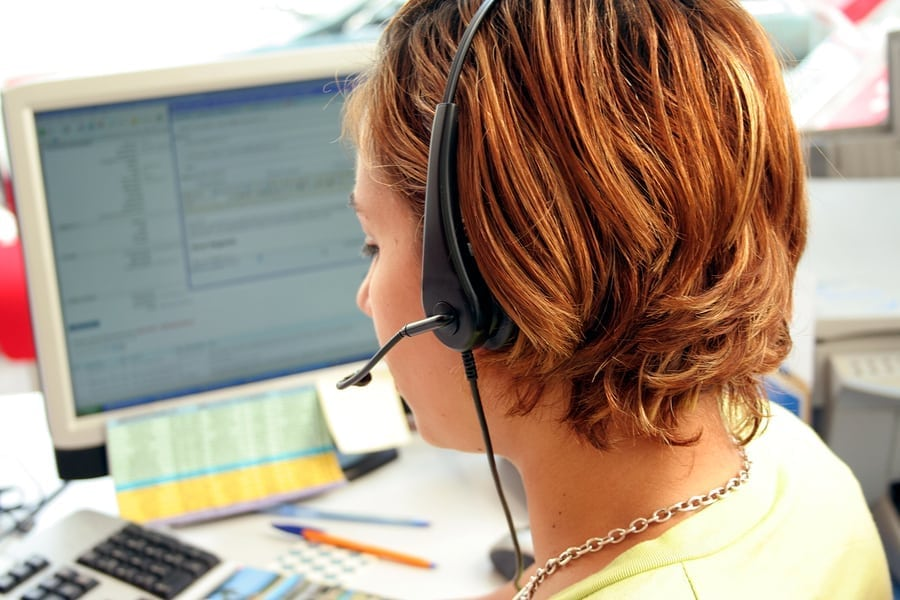 Young woman on a call center answering a phone ** Note: Slight blurriness, best at smaller sizes