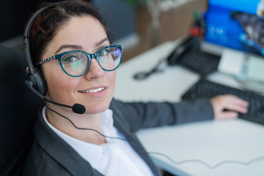 A friendly female call center operator at the desk. The woman in the headset answers the customers call.
